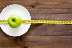 Proper nutrition with dietary fibre for weight loss. Apple on plate near measuring tape on dark wooden background top. View stock images