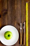 Proper nutrition with dietary fibre for weight loss. Apple on plate near measuring tape on dark wooden background top. View stock photography