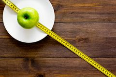 Proper nutrition with dietary fibre for weight loss. Apple on plate near measuring tape on dark wooden background top. View stock photo