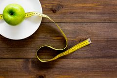 Proper nutrition with dietary fibre for weight loss. Apple on plate near measuring tape on dark wooden background top. View royalty free stock photography