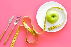 Proper nutrition with dietary fibre for weight loss. Apple on plate near measuring tape on pink background top view.  royalty free stock images