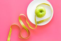 Proper nutrition with dietary fibre for weight loss. Apple on plate near measuring tape on pink background top view copy. Proper nutrition with dietary fibre for royalty free stock images