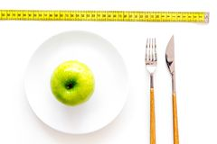 Proper nutrition with dietary fibre for weight loss. Apple on plate near measuring tape on white background top view.  royalty free stock images