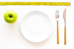 Proper nutrition with dietary fibre for weight loss. Apple on plate near measuring tape on white background top view.  stock images