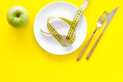 Proper nutrition with dietary fibre for weight loss. Apple on plate near measuring tape on yellow background top view.  royalty free stock images