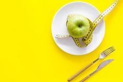 Proper nutrition with dietary fibre for weight loss. Apple on plate near measuring tape on yellow background top view.  stock photography