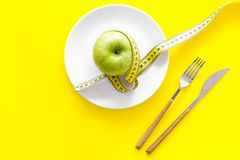Proper nutrition with dietary fibre for weight loss. Apple on plate near measuring tape on yellow background top view.  royalty free stock photos