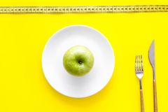 Proper nutrition with dietary fibre for weight loss. Apple on plate near measuring tape on yellow background top view.  stock images