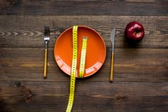 Proper nutrition for lose weight. Empty plate, apple and measuring tape on dark wooden background top view. Proper nutrition for lose weight. Empty plate and stock photo