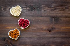 Proper nutrition for pathients with heart disease. Cholesterol reduce diet. Oatmeal, pomegranate, almond in heart shaped. Bowl on dark wooden background top royalty free stock photography