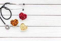 Proper nutrition for pathients with heart disease. Cholesterol reduce diet. Oatmeal, pomegranate, almond in heart shaped. Bowl near stethoscope on white stock photo