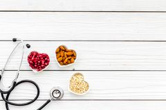 Proper nutrition for pathients with heart disease. Cholesterol reduce diet. Oatmeal, pomegranate, almond in heart shaped. Bowl near stethoscope on white stock photos