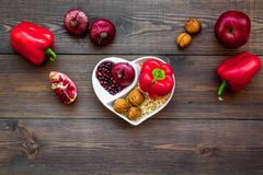 Proper nutrition for pathients with heart disease. Cholesterol reduce diet. Vegetables, fruits, nuts in heart shaped. Bowl on dark wooden background top view stock images