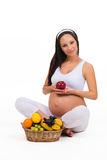 Proper nutrition during pregnancy. Vitamins and fruit. Pregnant women eating apple Stock Photo