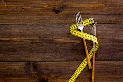Proper nutrition for slimming. Fork and knife with wound measuring tape on dark wooden background top view copy space stock photos