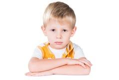 Proper ung pojke som sitter på den isolerade tabellen Royaltyfria Bilder