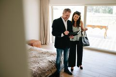Property adviser showing terms of contract to female buyer. Happy male real estate agent with client standing inside a new house and looking at documents Stock Image