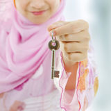 Property agent. Muslim woman hand holding a new key Stock Photos