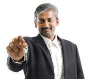 Property Agent. Mature adult Asian Indian man arm out holding a new key over white background Royalty Free Stock Photo