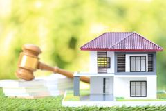 Property auction, Model house and Gavel wooden on natural green background, lawyer of home real estate and ownership property stock photo