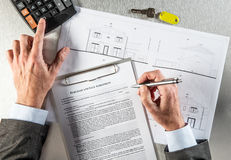 Property developer hands with architect blue print writing purchase agreement Royalty Free Stock Photography