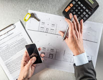 Property developer hands using his phone at the sale agreement Royalty Free Stock Image