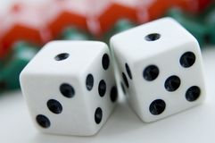 Property Gamble. Two dice show double ones in front of rows of plastic housing (shallow depth of field used Stock Photo
