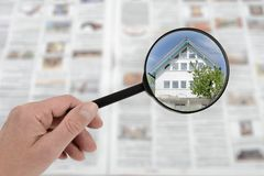Property immovable rental house search in housing market. Searching with magnifier for immovable property rental house in the housing market royalty free stock image