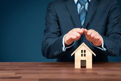 Property insurance. Property family house insurance protection concept. Insurance agent with wooden model of the house and protective gesture stock photography