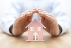 Property insurance. House miniature covered by hands. royalty free stock images