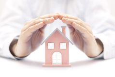 Property insurance. House miniature covered by hands. stock images