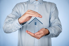 Property insurance. And security concept. Protecting gesture of man and symbol of house Royalty Free Stock Image