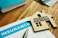 Free Property Insurance Stamp On A Model  Home Royalty Free Stock Photography - 151295357
