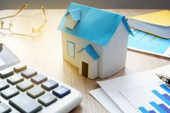 Property invest. Model of house and financial information about real estate market. Property invest concept. Model of house and financial information about real Stock Photo