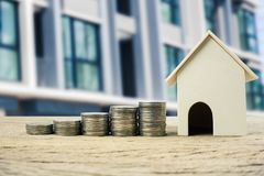 Property investment, home loan, house mortgage ,real estate financial concept. Money coin stack growing with wooden residential house model. Depicts a growth royalty free stock photo