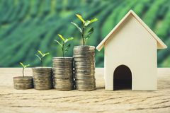 Property investment, home loan, house mortgage, real estate financial concept. Plant growing on stack coins with residential house model. Depicts a growth royalty free stock image