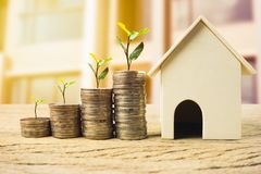 Property investment, home loan, house mortgage ,real estate financial concept. Plant on stack Money coins growing with wooden residential house model. Depicts stock photos