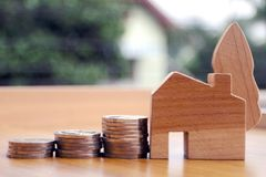 Property investment and house mortgage concept. Financial property investment and house mortgage concept. stacks of coins and wooden hand made house model on stock image