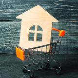Property investment and house mortgage financial concept. buying, renting and selling apartments. real estate. Wooden house in a. Shopping basket. credit royalty free stock photography