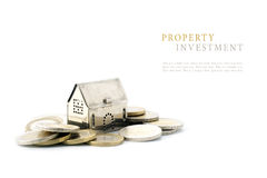 Property investment, silver golden house model on coins isolated. On white background, copyspace with sample text Stock Photo