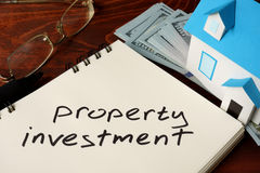 Property Investment. Written on notebook with model of house and dollars Stock Photography