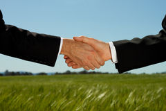 Property Land Deal. Two businessman shake hands with a land and property field background with plenty of copy space royalty free stock photos