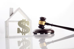 Property law. Gaval hammer with model house with dollar sign on the white background Stock Photos