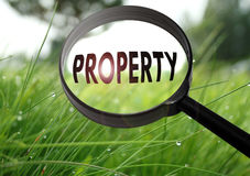 Property. Magnifying glass with the word property on grass background. Selective focus stock photos