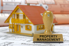 Property management printed on rubber stamp. With model house and plan Stock Photos