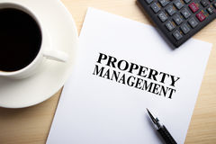Property Management. Text Property Management is on the white paper with coffee, calculator and ball pen aside Stock Photos