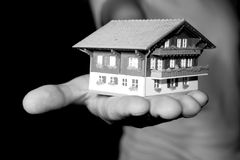 Property market. A man is holding a house in his hand Stock Image