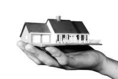Property market. A man is holding a house in his hand Royalty Free Stock Images