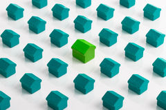 Property market and real estate. Real estate housing market conceptual image with a series of aqua blue houses surround an individual green house Royalty Free Stock Photos