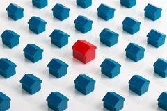 Property market and real estate. Real estate housing market conceptual image with a series of dark blue houses surround an individual red house Royalty Free Stock Image